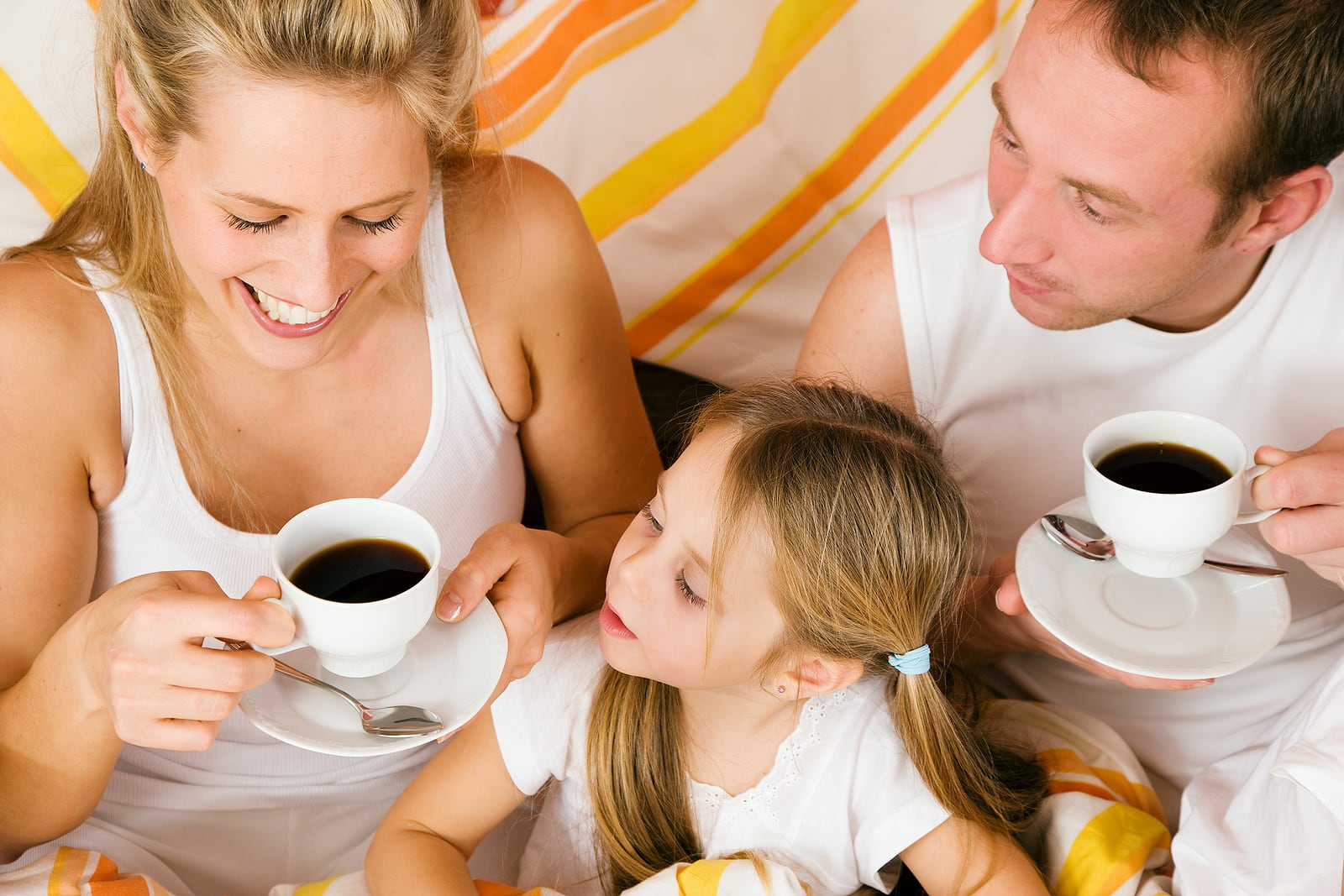 family drinking coffee in bed